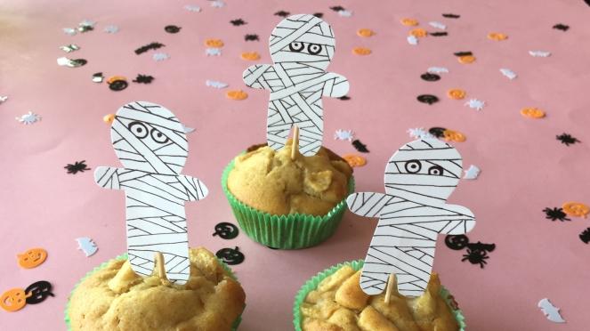 Im Bild sind drei Apfelmuffins mit grünem Muffinförmchen die mit einem selbstgemachten Cupcake-Topper in Mumienform für Halloween dekoriert sind.