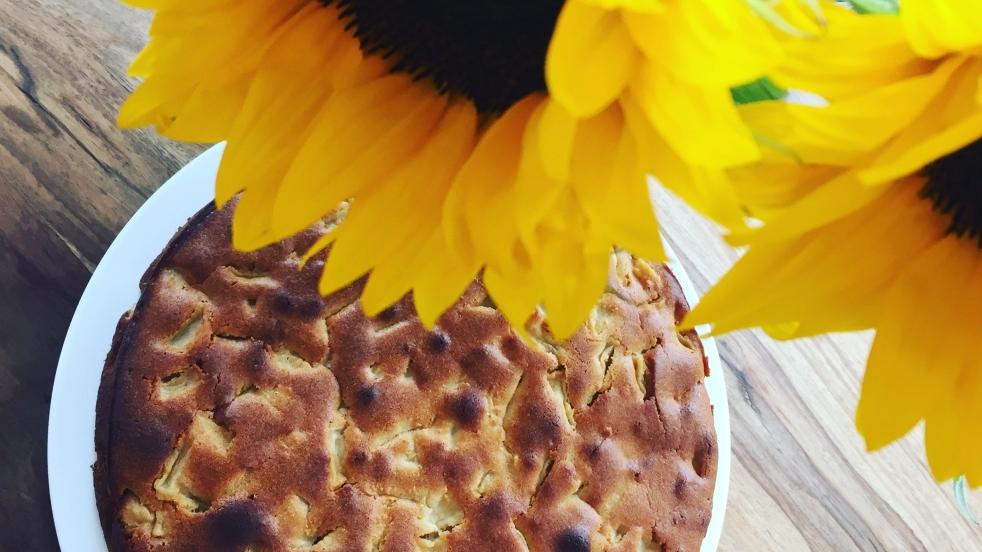 Ein brauner, fester Apfelkuchen ohne Zucker liegt auf einem weißen Teller auf einem Holztisch. Auf dem Tisch sind neben dem Kuchen Sonnenblumen dekoriert.