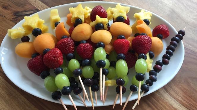 Auf einer weißen Servierplatte liegen viele Fruchtspieße. Das Obst auf den Spießen ist mit buntem Obst dekoriert. Von unten nach oben, eine Blaubeere, eine Weintraube, eine Blaubeere, eine Erdbeere, eine Blaubeere, eine Aprikose, eine Blaubeere und zum Schluss ein Stern mit einem Keksförmchen aus Ananas ausgestochen.