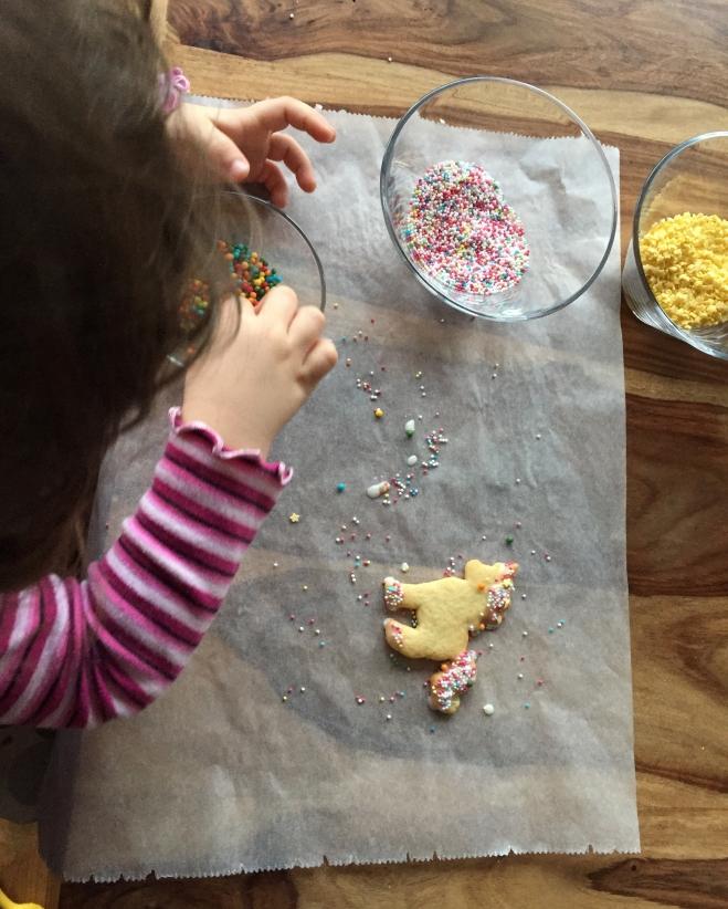 Ein Kind sitzt vor einem Kuchengitter mit einem Haufen umdekorierten Plätzchen drauf. Vor dem Gitter liegt ein Backpapier mit 3 Schüsseln mit verschiedenen bunten Streuseln und ein bereits dekoriertes Einhornplätzchen.