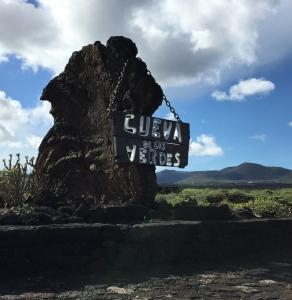 Ein Fels mit einem Holzschild auf dem 'Cueva de los Verdes' steht, steht auf einem grünen Feld mit strahlend blauem Himmel im Hintergrund.