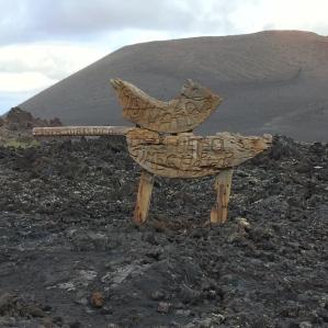 Ein kleines Kind steht vor dem aus Stahl gefertigten Feuerteufel des Nationalparks Timanfaya auf Lanzarote.