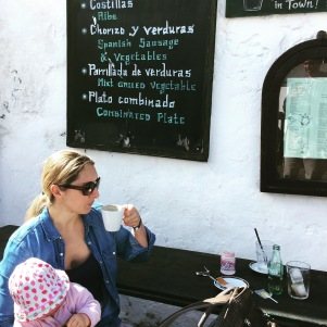Eine Frau sitzt mit einem Kleinkind auf dem Schoss an einem Tisch vor einer Bar und trinkt einen Kaffee aus einer weißen Kaffeetasse. Auf dem Tisch stehen die Reste einer Pause mit Kindern - Babyflasche, leere Wasserflasche und Gläser. Im Hintergrund hängt die Speisekarte an einer weissgekalkten Hauswand.