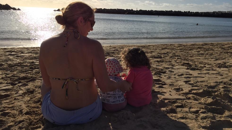 Auf dem Bild sitzt eine Frau mit zwei Kleinkindern am Sandstrand und im Hintergrund spiegelt sich die Untergehende Sonne auf dem Meer.