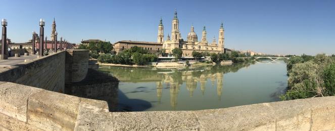 Das Bild zeigt einen Rundblick von der gegenüberliegenden Flußseite auf die El Pilar - die Kathedrale Zaragozas. Auf dem Bild sind zusätzlich der Fluss Ebro und die zwei zur Pilar führenden Brücken zu sehen.
