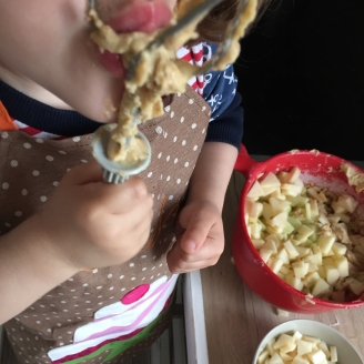 Ein Kind leckt die Mixerstäbe voller Teig ab. Im Hintergrund steht die Teigschüssel mit dem Apfelkuchenteig.