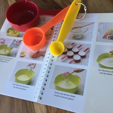 Es werden die Arbeitsschritte des Backbuchs der Kinderleichten Becherküche gezeigt, zusammen mit den Bechern.