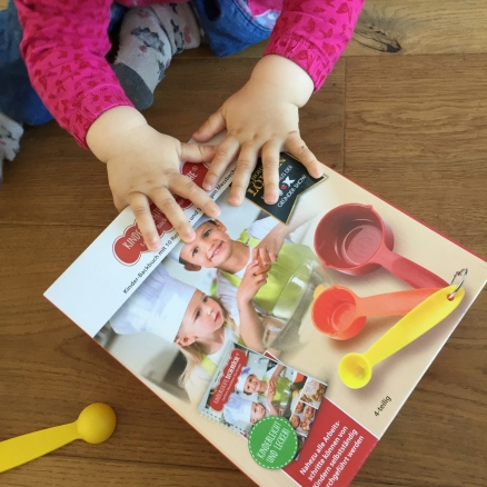 Auf dem Bild ist die Verpackung des Bechersets der kinderleichten Becherküche zu sehen. Ein Kleinkind hält die bunten Becher des Sets in der Hand.