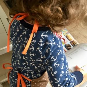 Ein Kind mit blauem Kleid mit weißen Ankern drauf blättert auch durch das Backbuch der kinderleichten Becherküche.