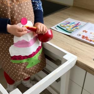 Ein Kind mit einer braunen Schürze, auf der ein Kuchen aufgenäht ist, hält die Becher der Kinderleichten Becherküche in der Hand. Auf der Arbeitsplatte hinter dem Kind liegt das aufgeschlagene Backbuch.