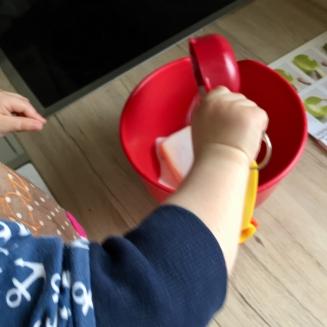 Ein Kind schüttet mit einem roten Becher der kinderleichten Becherküche Zucker in eine rote Schüssel.