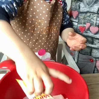 Das Bild zeigt eine Schüssel im Vordergrund die von einem Kleinen Kind im Lernstuhl mit Backpulver gefüllt wird.