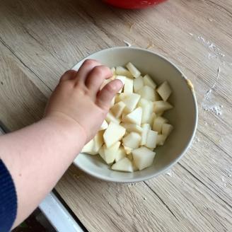Das Bild zeigt wie eine kleine Hand Apfelstückchen aus einer Schüssel mit klein geschnittenen Apfelstückchen von einer bemehlten Arbeitsplatte nascht.