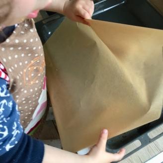 Ein Kind legt ein Backblech mit Backpapier aus.