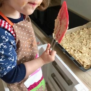 Ein Kind steht im Lernstuhl vor dem noch angebackenen Blech Apfelkuchen aus der kinderleichten Becherküche und nascht Teig vom Küchenschaber.