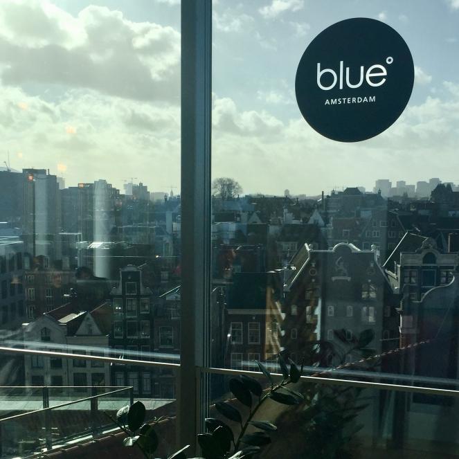 Das Bild zeigt die Aussicht aus dem Café Blue Amsterdam durch eine Glasscheibe. Unterhalb des Cafés erstreckt sich Amsterdam.
