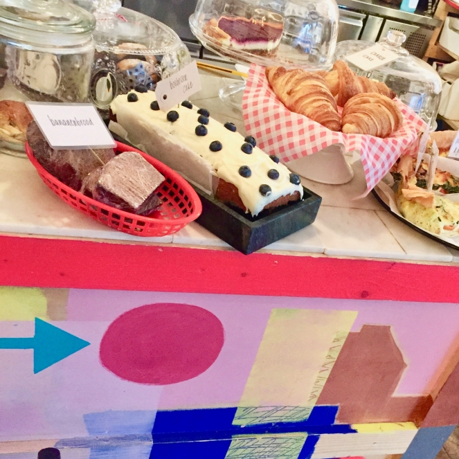Auf dem Bild ist eine CaféTheke mit Kuchen, Croissants und anderen Köstlichkeiten zu sehen.