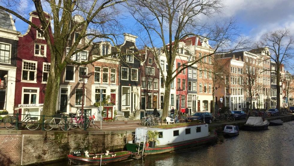 Das Bild ist an einem sonnigen Tag in Amsterdam aufgenommen und zeigt eine Gracht mit Hausbooten und daran anschließender Häuserfront.