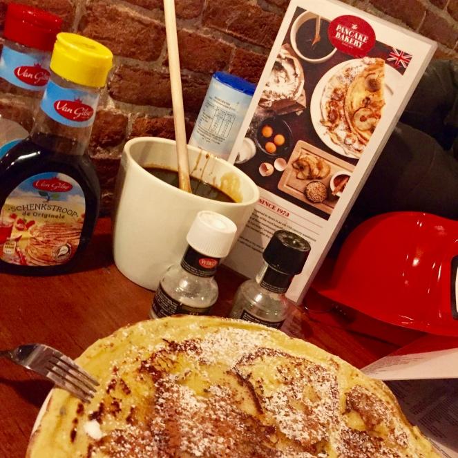 Auf dem Bild ist ein typisch holländischer Pfannkuchen auf einem Tisch zu sehen. Hinter dem Pfannkuchen stehen eine Speisekarte und alle typischen Dopings wie Zimt und Zucker, Ahornsirup.
