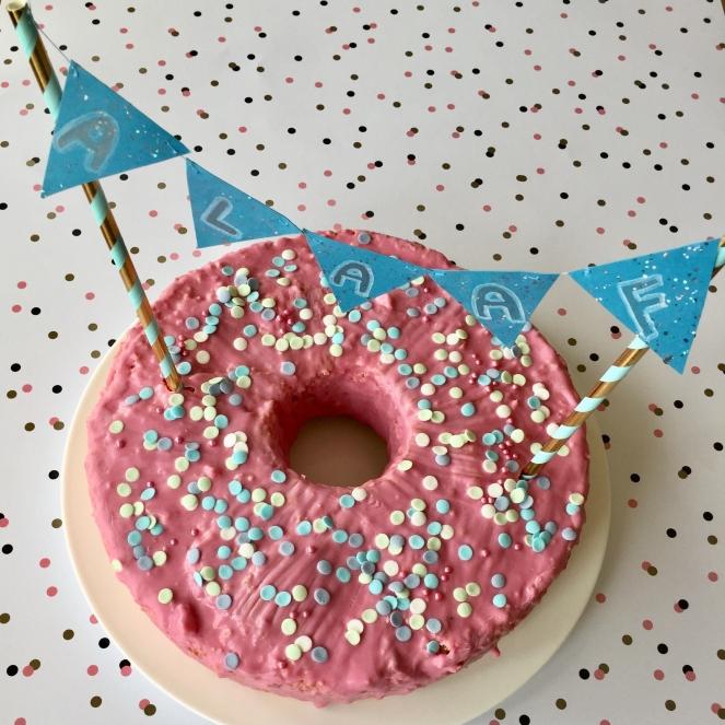 Auf einem gepunkteten weißen Untergrund steht ein pinker, flacher Gugelhupf, der mit Konfettizuckerperlen verziert ist. Auf dem Kuchen befindet sich eine kleine Wimpelkette mit der Aufschrift ALAAF.