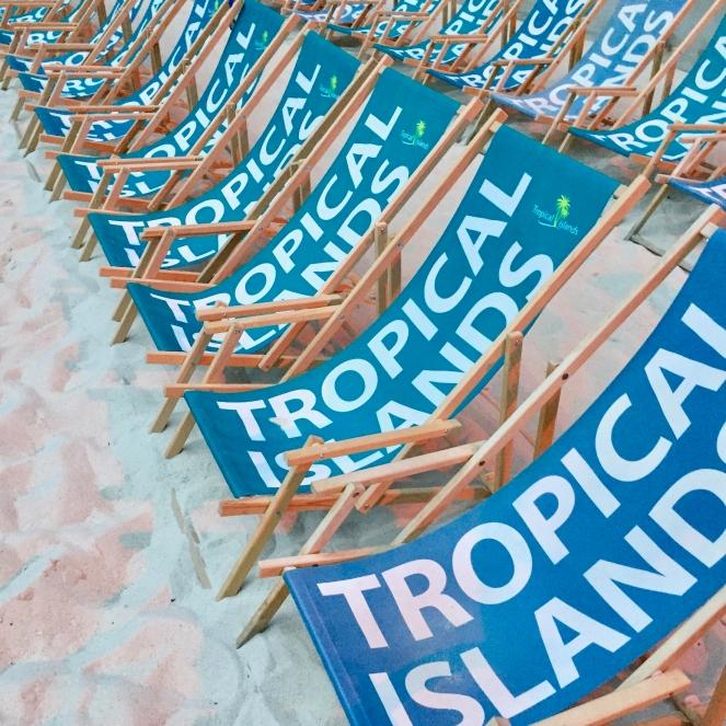 Das Bild zeigt zwei Reihen leerer, blauer Liegestühle mit dem Schriftzug Tropical Island auf weißem Sandstrand.