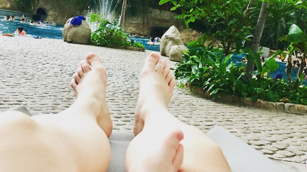 Auf dem Bild sind Füße eines Erwachsenen zu sehen, der offensichtlich ein Kleinkind auf dem Schoß hat, da auch dessen Füße zusehen sind. Im Hintergrund sieht man die Lagune der Badelandschaft Tropical Island in Berlin.