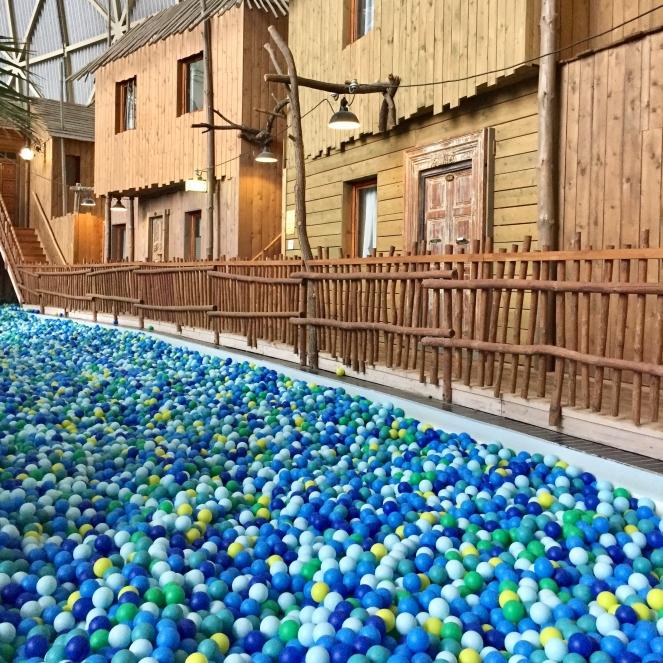 Im Vordergrund ist ein riesiges Bällebad mit Bällen in hellblau, blau udnn grün zu sehen, im Hintergrund steht eine Holzhüttenreihe.