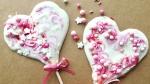 Auf Paperbraunem Hintergrund liegen zwei aus weißer Schokolade gegossene Herzlollis. Sie sind mit rosa eingefärbter Schokolade marmoriert und mit Zuckerperlen geschmückt.