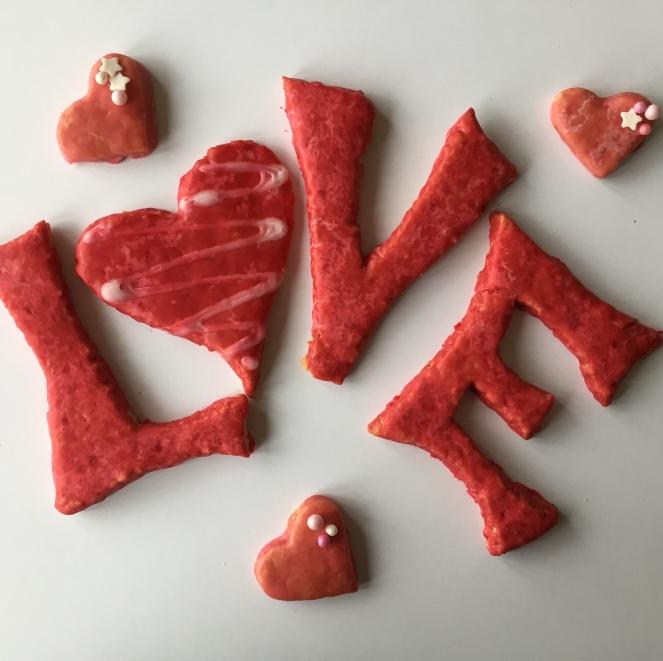 Auf dem Bild sind rot eingefärbte Kekse zu sehen, die zusammen das Wort LOVE ergeben. Dekoriert mit Herzchenkeksen.