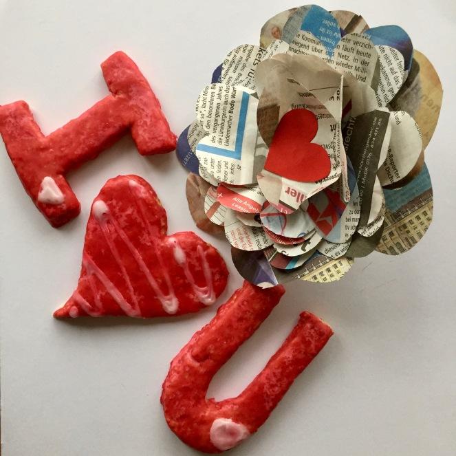 Auf dem Bild sind drei rot eingefärbte Kekse zu sehen, ein I ein Herz und ein U - I love you! Dekoriert mit einer Papierrose