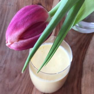 Im Vordergrund ist eine pinke Tulpe hinter der ein Glas mit einem Mango Lassi hervorscheint.