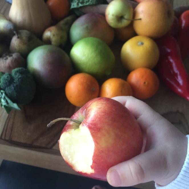 Das Bild zeigt eine Ansicht auf viele verschiedene Obst- und Gemüseteile, die in ihrer Optik nicht perfekt sind. Ein Kind hält einen angebissenen Apfel in die Kamera.