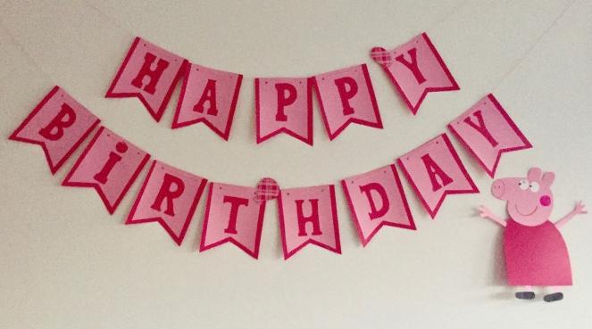 """An einer weißen Wand hängt eine rosa-Pink Farbene Wimpelgirlande aus Papier mit der Aufschrift """"Happy Birthday"""". Unten Rechts hängt eine gebastelte Peppa Pig in einem Roten Kleid und hochgereckten Armen."""