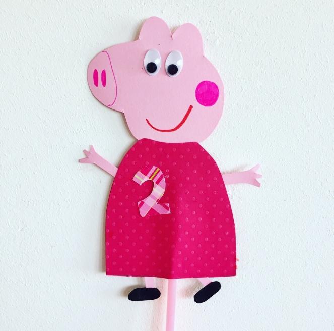 Vor weißem Hintergrund ist eine gebasteltes Schweinchen mit rotem Kleid zu sehen. Peppa Pig. Sie hat Wackelaugen und eine zwei auf dem roten Kleidchen. Die Figur ist auf einen Strohhalm geklebt, damit sie auf einen Kuchen gesteckt werden kann.