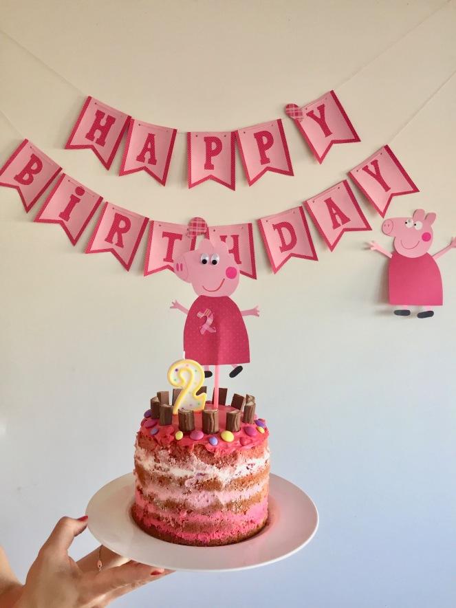 Im Vordergrund wird eine rosa-weiß dekorierte Peppa Pig Torte von einer Hand mit rotem Nagellack in die Kamera gehalten. Ein Kerze in der Form einer Zwei und ein Caketopper in Schweinchenform, Peppa Pig, krönen die Torte. Im Hintergrund hängt einen Happy Birthday Papiergirlande und ein gebasteltes Schweinchen im roten Kleidchen.
