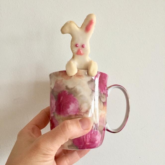Vor einem weißen Hintergrund wird eine rosa geblümte Tasse in die Luft gehalten, an der sich ein Hasenplätzchen festhält und hinausschaut.