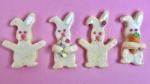 Auf rosa Hintergrund liegen vier Hasenplätzchen, die mit Zuckergruss und Perlen dekoriert sind. Ein Hase trägt ein Osterei aus Zuckerperlen, eins eine Marzipanmöhre und die zwei anderen haben die Arme in die Luft gestreckt.