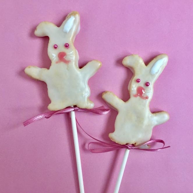 Auf Rosa Hintergrund liegen zwei mit Zuckerguss dekorierte Hasenplätzchen, die auf einen Schaschlik gespiesst sind und mit einer Schleife als Lolli dekoriert sind.