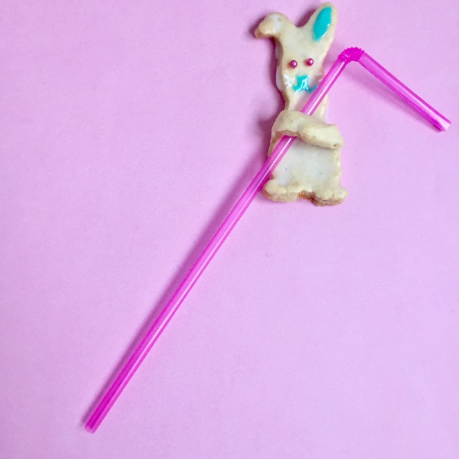 Auf einem rosa Hintergrund hält sich ein Hasenplätzchen an einem pinken Strohhalm fest.