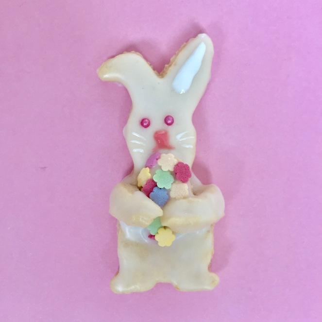 Auf Rosa Hintergrund liegt ein mit Zuckerguss dekoriertes Hasenplätzchen, das ein Osterei aus Zuckerperlen in der Hand hält.