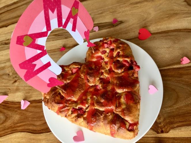 Ein Hefeschnecken-Kuchen mit Erdbeeren ist auf einem Weißen Teller angerichtet. Der Kuchen ist mit einem Caketopper in Regenformoptik in rosa gehalten dekoriert. Um den Teller liegen rosa Papierherzen. Der Kuchen steht auf einem Holztisch.