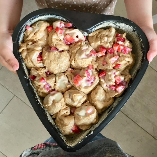 Das Bild zeigt den Blick auf eine Herzbackform, die mit vielen Hefeschnecken mit Erdbeerstückchen gefüllt ist und von einem Kind in die Kamera gehalten wird.