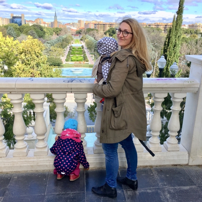 Auf dem Bild steht eine Frau mit einem Kind vor der Brust in der Trage und einem Kind zu ihren Füssen, dass den Berg hinunter auf den Park schaut. Im Hintergrund sind die angelegten Gärten des Parks und noch weiter im Hintergrund die Stadt Zaragoza zu sehen.