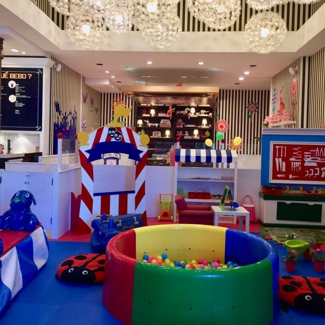 Das Bild zeigt eine bunte Spielecke mit Kaufladen, Bällebad, Puppentheater und Werkbank in einem Café für Familien.