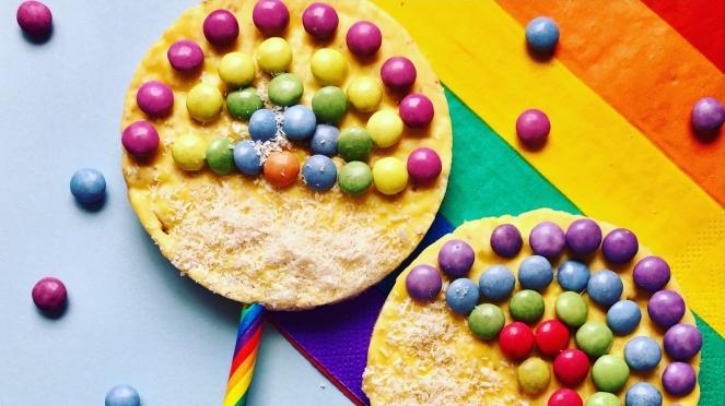 Zwei Reiswaffeln sind auf jeweils einen regenbogenfarbenen Papierstrohhalm gesteckt. Auf die Waffeln ist mit Smarties ein Regenbogen dekoriert. Die Waffeln liegen auf einer bunten Regenbogenservierte.