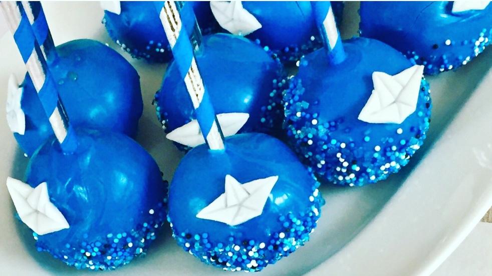Dunkelblaue Cakepops mit silber-blauem-Papierstrohhalm-Stiel dekoriert mit blauen und hellblauen Zuckerperlen als Meer und einem weißen Papierboot aus Fondant ausgestanzt auf einem weißen Servierteller