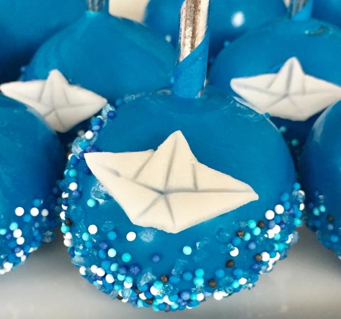 Großaufnahme eines dunkelblauen Maritimen-Cakepop mit blau-weißen Zuckerperlen als Meer und weißen Fondantschiffchen dekoriert. Im Hintergrund befinden sich weitere Cakepops.