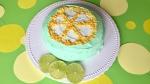 Limettenkuchen mit Creme dekoriert wie eine aufgeschnittene Limette auf einer weißen Tortenplatte am Rand dekoriert mit drei frischen Limettenscheiben auf grasgrünen Untergrund mit großen gelben Punkten.