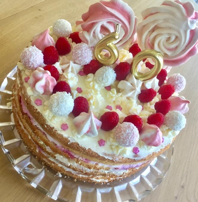 rosa-weiß dekorierte Torte auf einem Glasteller. Die Torte ist mit Raffaelos, Baiserlollies und -drops und frischen Himbeeren und einer goldenen Kerze geschmückt.
