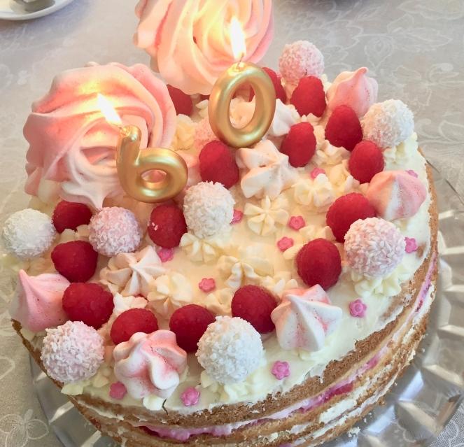 Eine rosa-weiße Geburtstagstorte zum 60. Geburtstag mit brennenden Kerzen und mit Baiserlollis, -drops, Frischen Himbeeren und Raffaelos ist auf einer Kaffeetafel zu sehen.